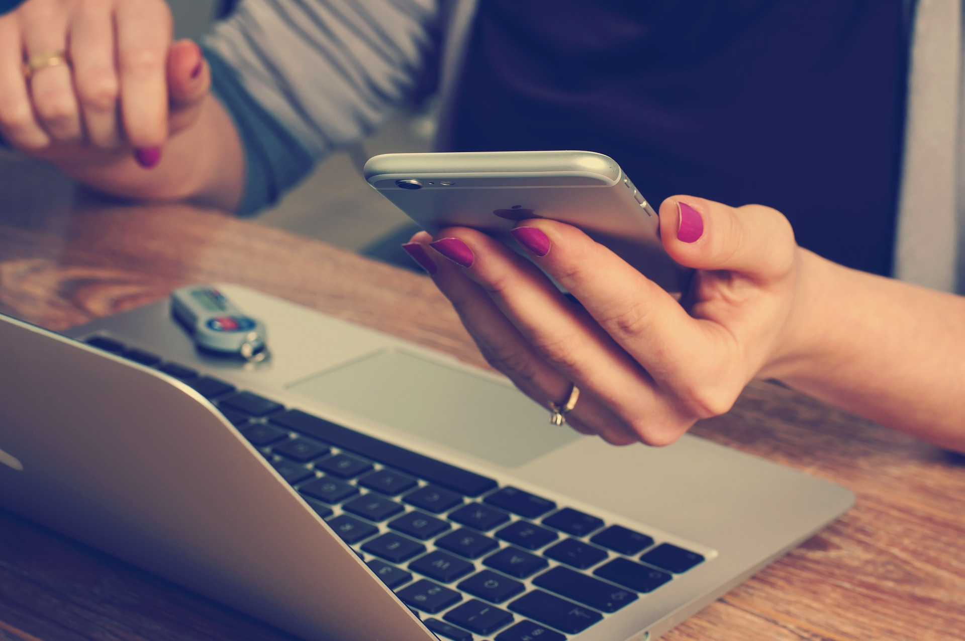 Main qui tient un smartphone devant un ordinateur mac