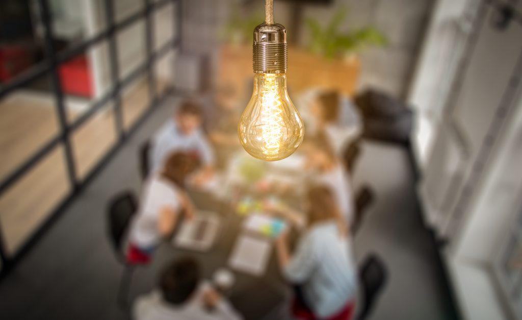 ampoule allumée au dessus d'une équipe qui réfléchit sur un blog b to b