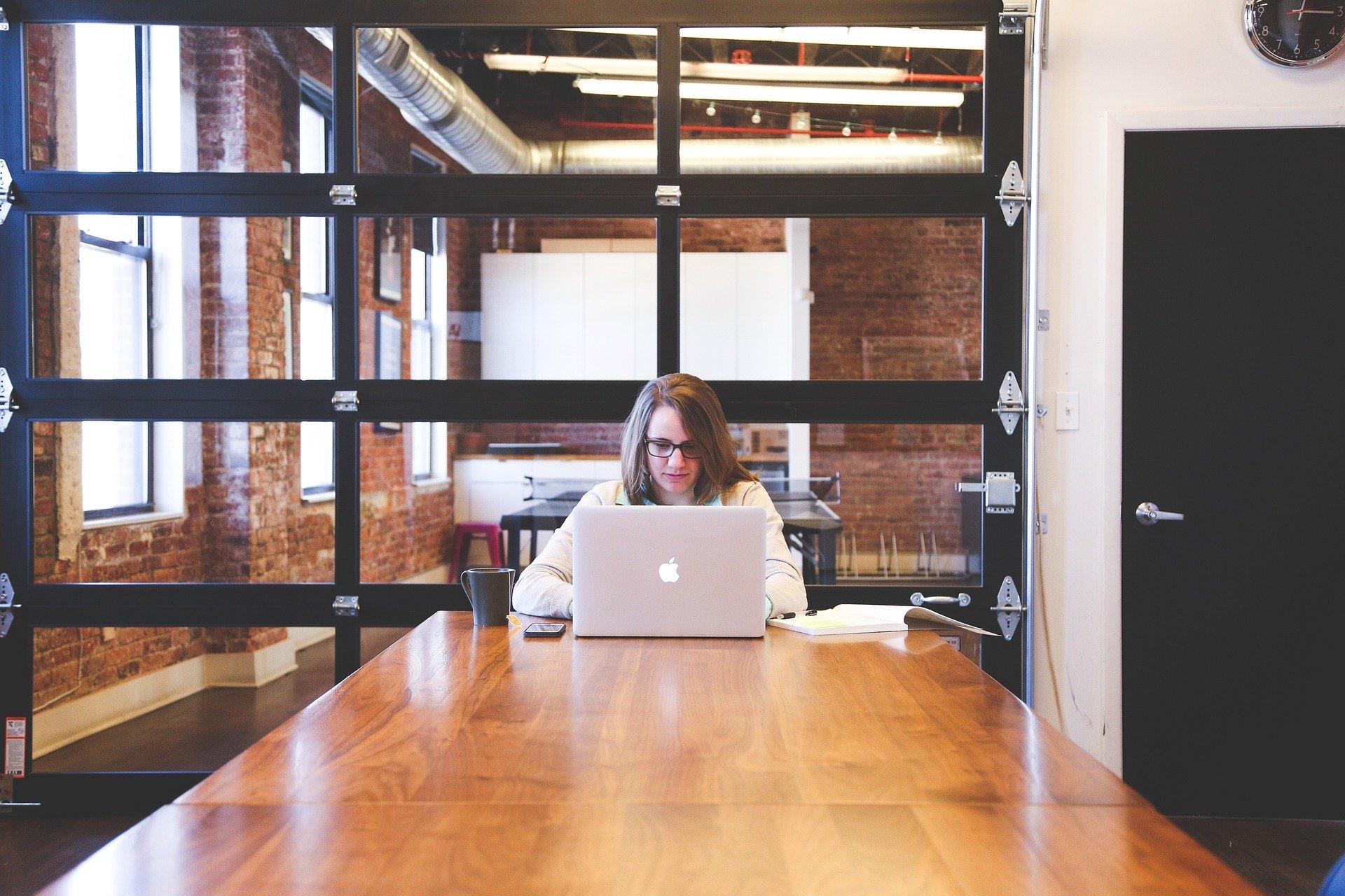 Télétravail femme seule dans grand espace de verre avec son macbook en télétravail