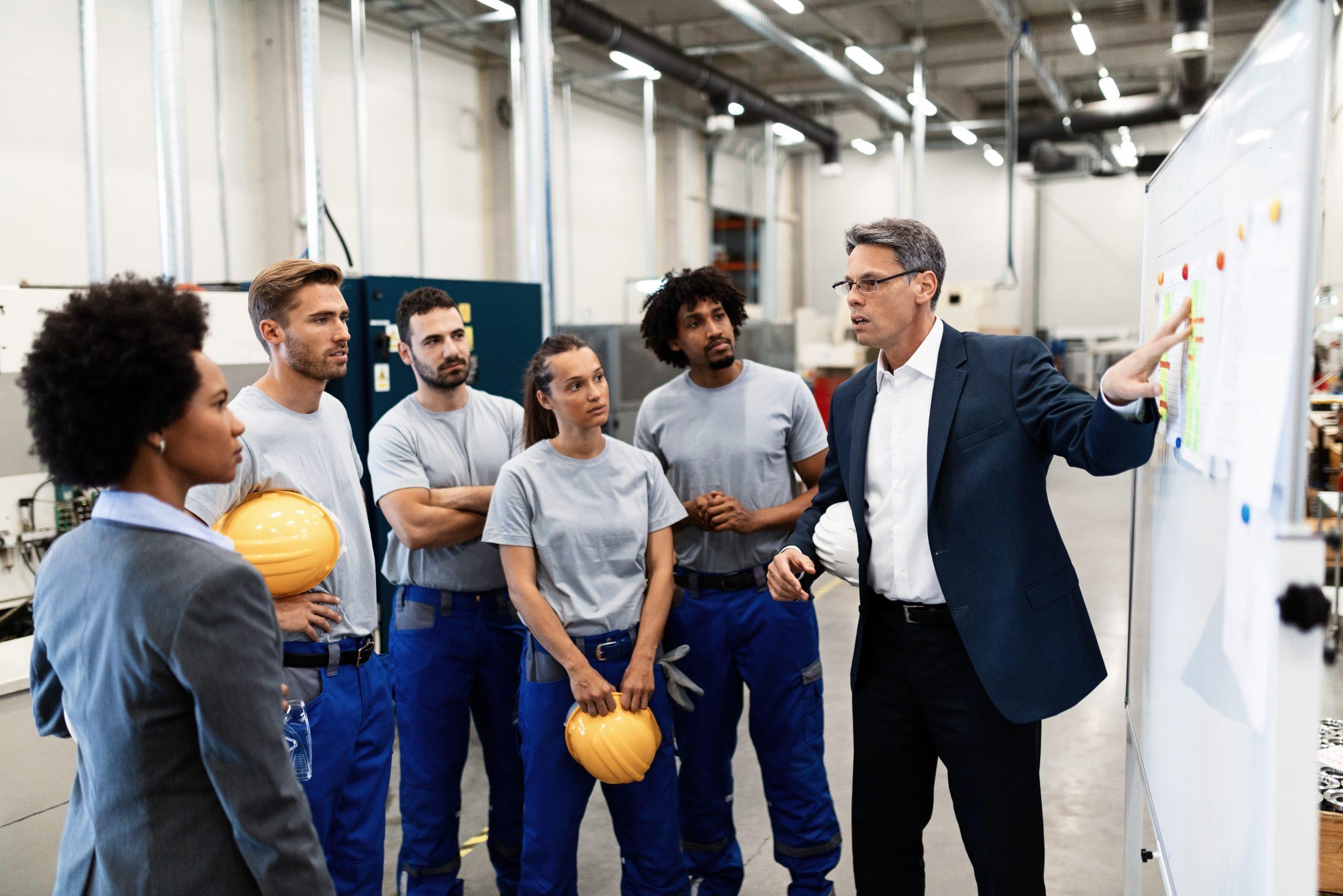Homme indique un panneau à un groupe de jeune avec des casques de chantier le fonctionnement en mode agile