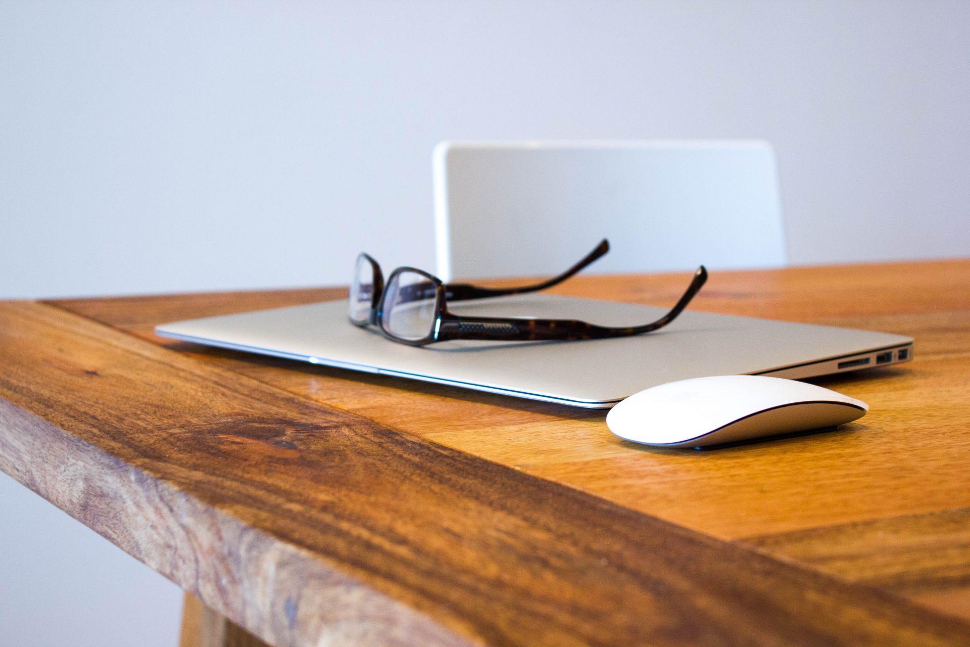 Ordinateur fermé posé sur une talble en bois avec des lunettes posées dessus et une souris d'ordinateur