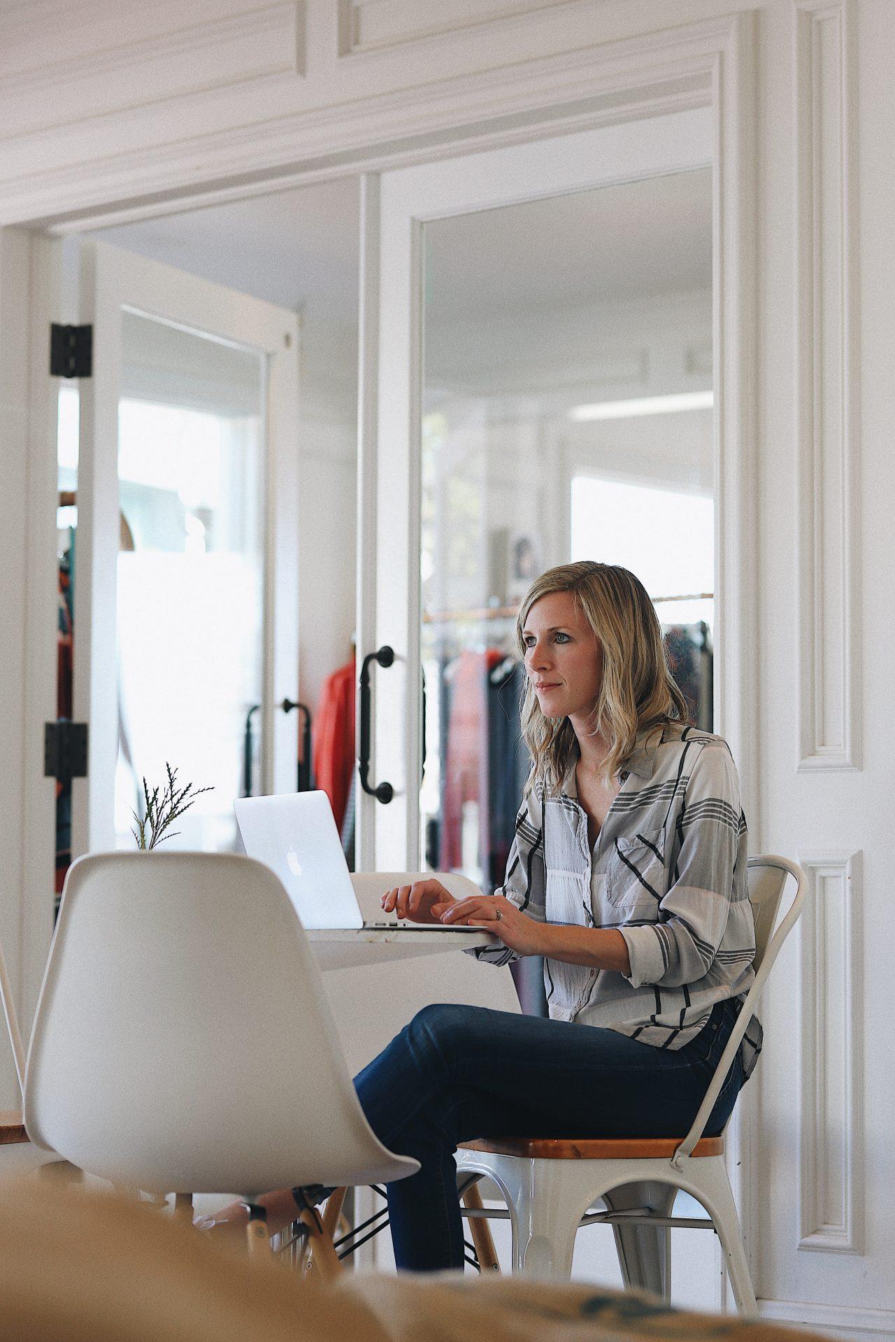 femme blonde assise sur un fauteuil dans sa boutique tape sur son ordinateur
