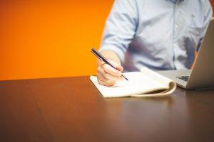 homme seul en formation elearning écrit avec un stylo sur un cahier