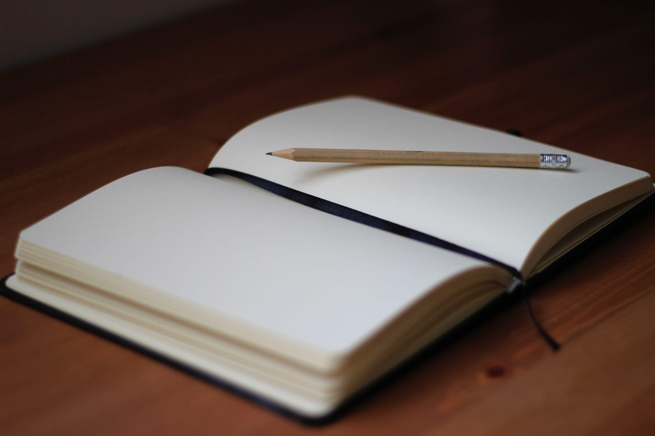 carnet sur un bureau avec un crayon posé dessus