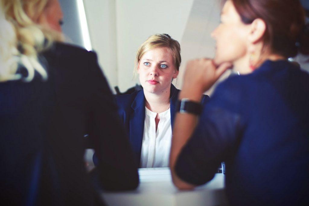 une femme fait face à deux autres femmes pour un entretien
