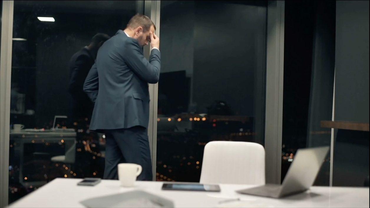 Homme en costume et debout dans son bureau se tient la tête