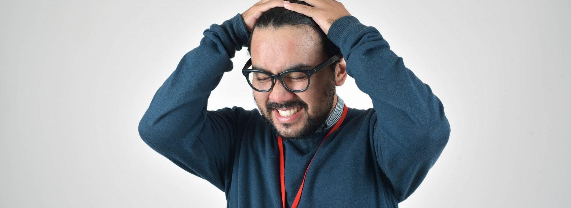 Homme en pull bleu se tient la tête avec les deux mains et grimace